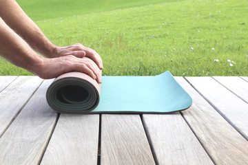 man rolling his yoga mat on a terrace