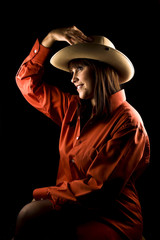 Portrait of young and attractive woman in red shirt and hat isolated on black background. She is having fun.