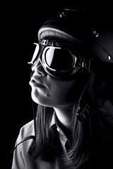 Portrait of emotional young woman with helmet and goggles isolated on black background. Close up.