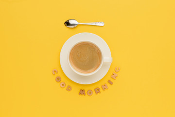 Top view of cup of fresh hot coffee and good morning inscription isolated on yellow