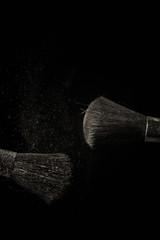 Make up brush with purple dust on black background