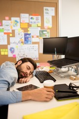 Tired businessman napping in creative office
