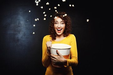 Laughing woman throwing up popcorn up in the air