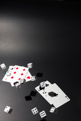 Dice fall over a set of cards on black background.