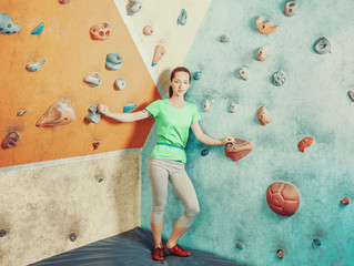 Sporty woman standing in climbing gym.