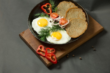 Homemade food. Tasty breakfast. Appetizing fried egg with potato pancakes and herbs in dripping pan  on a black background.