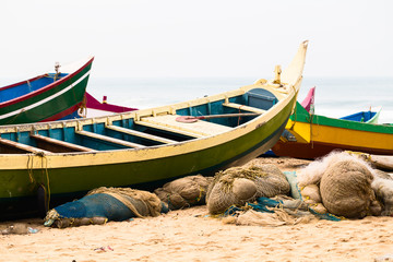 Fishing colorful boats and nets on the beach.