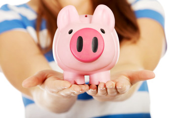 Teenage woman holding pink piggybank