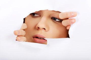 Teenage woman peeping through hole on paper