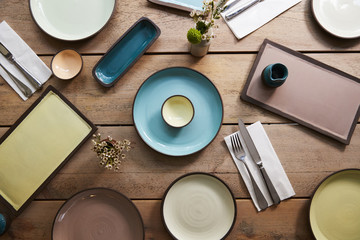 Handmade earthenware and cutlery on a table, overhead shot