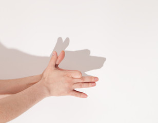 shadows from the hand on white wall