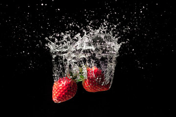 Strawberry fruit creating a beautiful splash underwater with black background