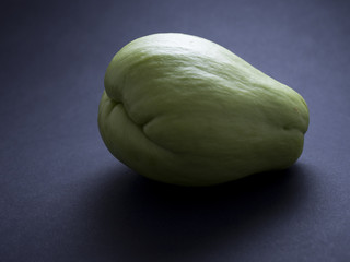 Chouchou fruit, also called mirliton or chayote, isolated on black background