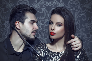Sexy woman with red lips seducing young rich man portrait