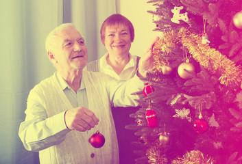 Elderly couple decorate fir-tree