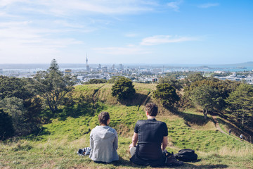 The young couple take a holiday time on the summit of mount Eden for seeing panorama view of Auckland town, North Island, New Zealand.