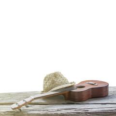 close-up ukulele and hat on wood and white background. over light .