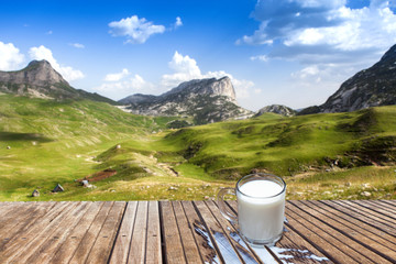 Mug of milk on a wooden table in the mountains. View of the small farm.