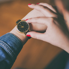 detail shot. young girl checking the time on her trendy and elegant wrist watch.