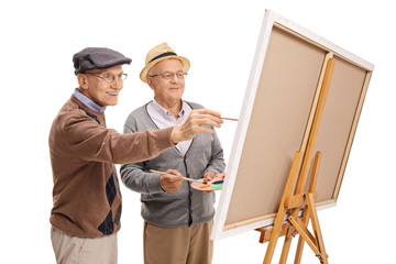 Two elderly men painting on a canvas