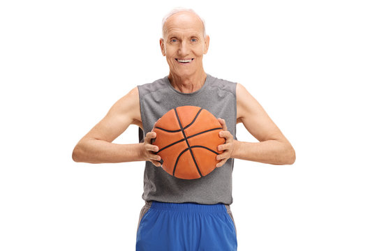 Senior with a basketball looking at the camera and smiling
