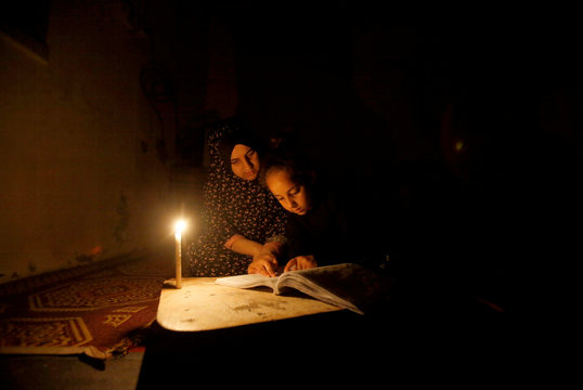 Palestinian girl studies her lessons by a candlelight during power cut inside her family's house at Shati refugee camp in Gaza City