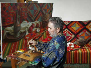 Adult painter draws the ethnical still life picture by oil paint in art workshop