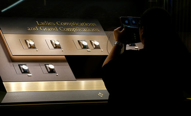 A woman takes a picture of watches at a display window of Patek Philippe at the Baselworld watch and jewellery fair in Base