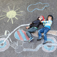 Two kid boys in helmet with motorcycle picture drawing with colo