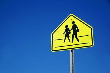 school crossing sign against sky