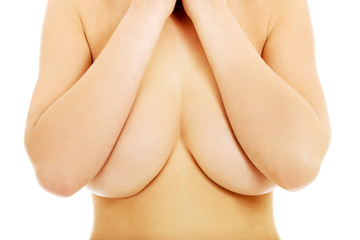 Topless slim woman covering her breast