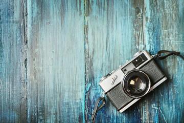 Vintage photo camera on grunge wooden background