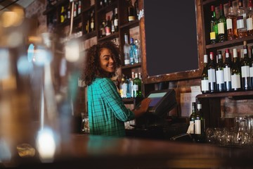 Portrait of beautiful female bar tender using electronic machine