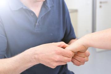 Orthopäde untersucht Handgelenk