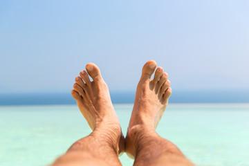 male feet on beach