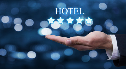 Hand holding five stars and inscription Hotel.