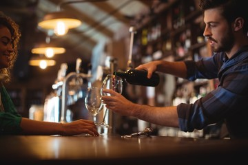 Male bar tender pouring wine in glasses