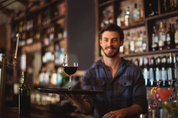 Portrait of bar tender holding a tray with glass of red wine