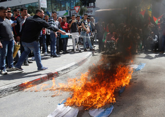 Palestinian demonstrators burn an Israeli flag during a rally in support of Palestinian prisoners on hunger strike in Israeli jails, in the West Bank city of Nablus