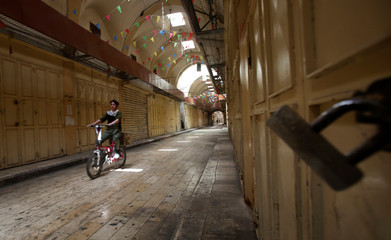 A Palestinian rides his bicycle past closed shops during a general strike in support of Palestinian prisoners on hunger strike in Israeli jails, in the old market of the West Bank city of Nablus