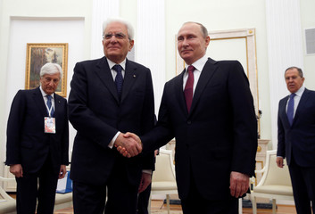 Russian President Vladimir Putin shakes hands with Italian President Sergio Mattarella during their meeting at the Kremlin in Moscow