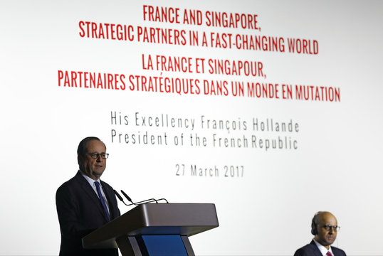 French President Hollande speaks at a public lecture next to Singapore's Deputy Prime Minister Shanmugaratnam in Singapore