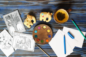 Many postcard in doodling style with drawn picture, pencils, pen and ceramic cup with tea lemon and two fabric toy small elephants on wooden blue background