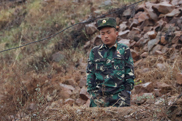 A North Korean soldier stands on guard at the Yalu River in Sinuiju, North Korea, which borders Dandong