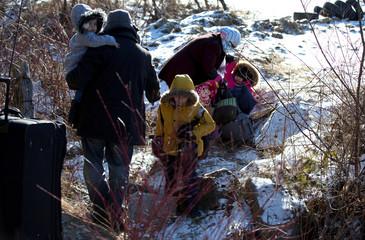 A family crosses the U.S.-Canada border leading into Hemmingford, Quebec, Canada