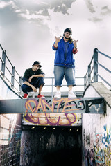 Two rap singers on a concrete beam with graffiti in the background
