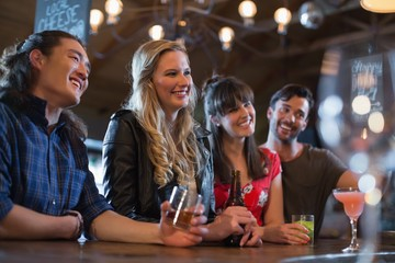 Smiling friends counter looking away in pub