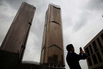 A businessman takes pictures of recently erected office and residential buildings in Beijing