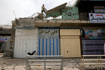 A worker removes rubble during the rebuilding of a building destroyed during fighting between Iraqi forces and Islamic state fighters, eastern Mosul