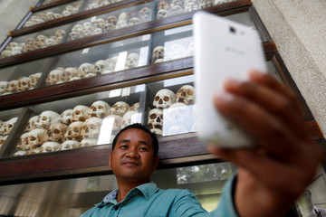 A man takes a picture in front of a glass case containing 5,000 human skulls belonging to the Khmer Rouge victims as people gather to mark the 42nd anniversary of the start of the regime at the Choeung Ek memorial in Phnom Penh